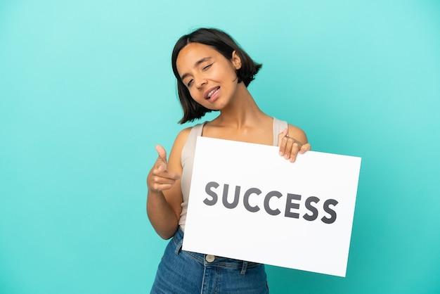 Młoda kobieta rasy mieszanej na białym tle na niebieskim tle trzymająca tabliczkę z tekstem sukces i wskazującą do przodu
