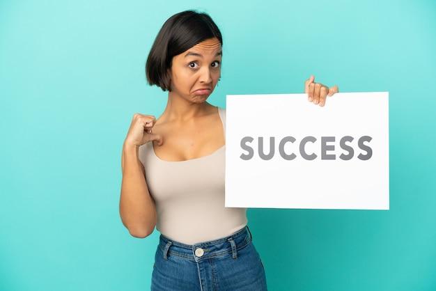 Młoda kobieta rasy mieszanej na białym tle na niebieskim tle trzymająca tabliczkę z tekstem sukces z dumnym gestem