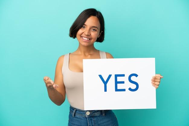 Młoda kobieta rasy mieszanej na białym tle na niebieskim tle trzymająca tabliczkę z tekstem tak, dokonując transakcji