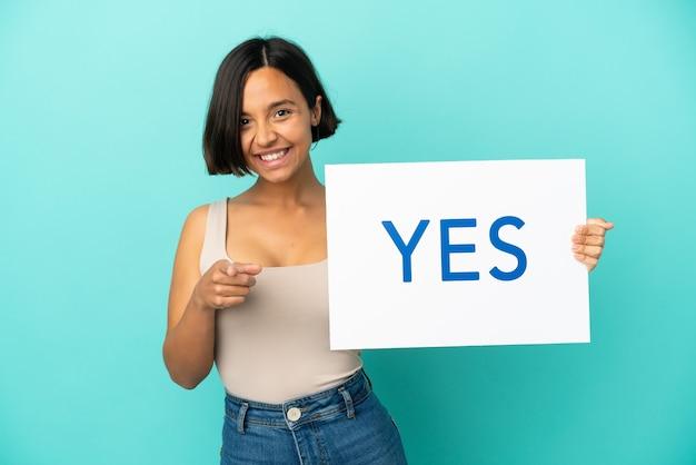 Młoda kobieta rasy mieszanej na białym tle na niebieskim tle trzymająca tabliczkę z tekstem tak i wskazującą go