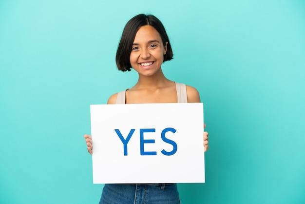 Młoda kobieta rasy mieszanej na białym tle na niebieskim tle trzymająca tabliczkę z tekstem tak ze szczęśliwym wyrazem