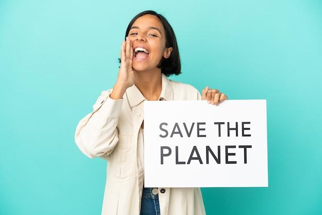 """Młoda kobieta rasy mieszanej na białym tle na niebieskim tle trzymająca tabliczkę z tekstem """"uratuj planetę i krzycząc"""