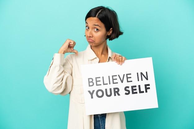 Młoda kobieta rasy mieszanej na białym tle na niebieskim tle trzymająca tabliczkę z tekstem wierz w siebie z dumnym gestem