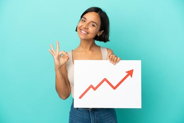 Młoda kobieta rasy mieszanej na białym tle na niebieskim tle trzymająca znak z rosnącym symbolem strzałki statystyk z ok znakiem
