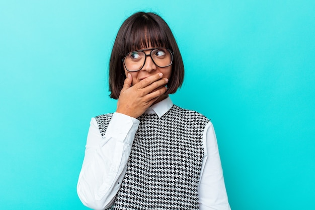 Młoda kobieta rasy mieszanej na białym tle na niebieskim tle zamyślony patrząc na kopię miejsca obejmujące usta ręką.