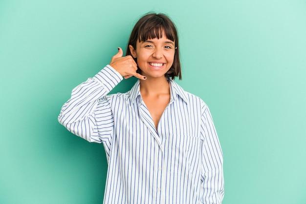 Młoda kobieta rasy mieszanej na białym tle na niebiesko pokazując gest połączenia z telefonu komórkowego palcami.