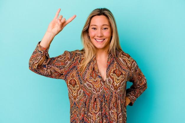 Młoda kobieta rasy mieszanej na białym tle na niebiesko pokazując gest rocka palcami