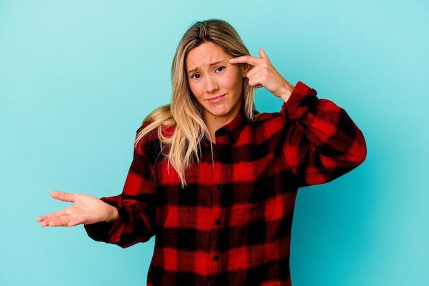 Młoda kobieta rasy mieszanej na białym tle na niebiesko pokazując gest rozczarowania palcem wskazującym.