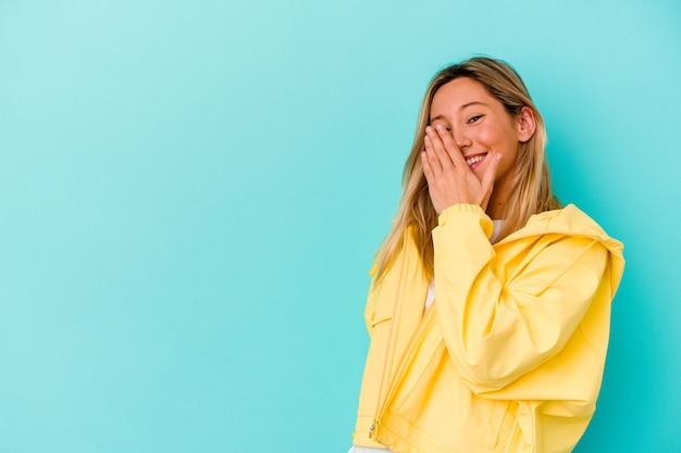 Młoda kobieta rasy mieszanej na białym tle na niebiesko śmiejąc się szczęśliwe, beztroskie, naturalne emocje.