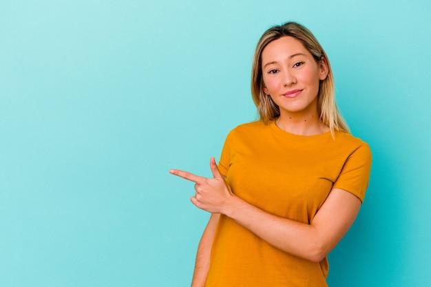 Młoda kobieta rasy mieszanej na białym tle na niebiesko, uśmiechając się i wskazując na bok, pokazując coś w pustej przestrzeni.