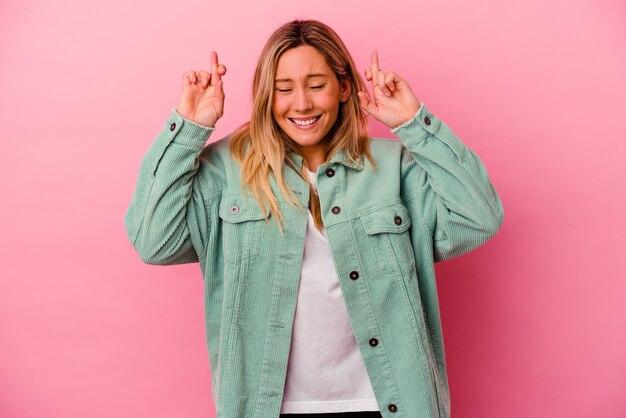 Młoda kobieta rasy mieszanej na białym tle na różowej ścianie kciuki za szczęście