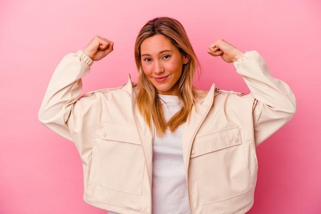 Młoda kobieta rasy mieszanej na białym tle na różowej ścianie pokazuje gest siły z rękami, symbol kobiecej mocy