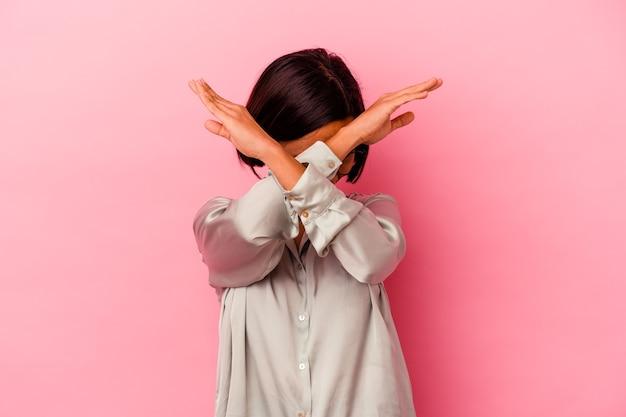 Młoda kobieta rasy mieszanej na białym tle na różowej ścianie, trzymając skrzyżowane ręce, koncepcja odmowy.