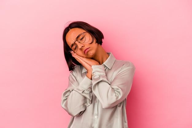 Młoda kobieta rasy mieszanej na białym tle na różowej ścianie ziewanie pokazując zmęczony gest obejmujący usta ręką.