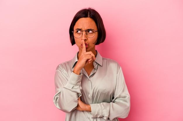 Młoda kobieta rasy mieszanej na białym tle na różowym tle dochowując tajemnicy lub prosząc o ciszę.
