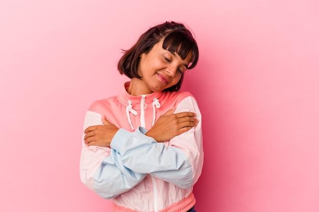 Młoda kobieta rasy mieszanej na białym tle na różowym tle przytula się, uśmiechając się beztrosko i szczęśliwie.