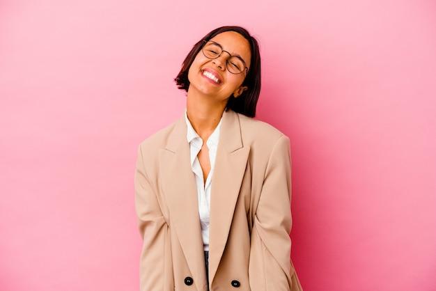 Młoda kobieta rasy mieszanej na białym tle na różowym tle śmieje się i zamyka oczy, czuje się zrelaksowana i szczęśliwa.