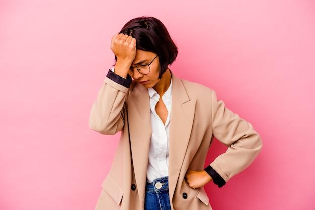 Młoda kobieta rasy mieszanej na białym tle na różowym tle zapominając o czymś, uderzając dłonią w czoło i zamykając oczy.