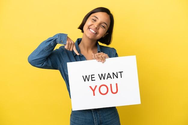 Młoda kobieta rasy mieszanej na białym tle na żółtym tle gospodarstwa we want you pokładzie i wskazując go