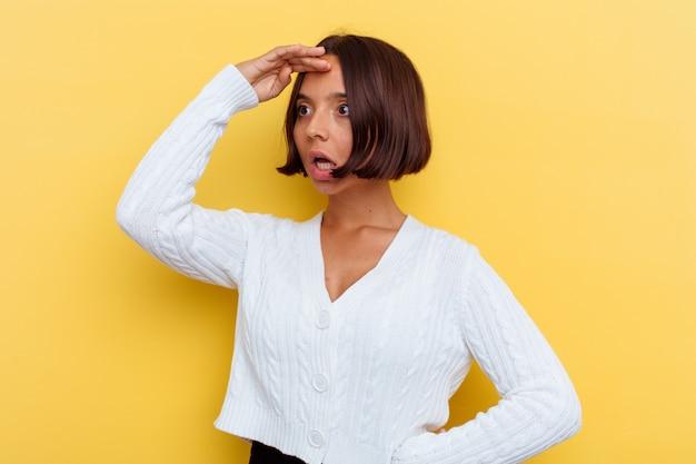 Młoda kobieta rasy mieszanej na białym tle na żółtym tle, patrząc daleko, trzymając rękę na czole.