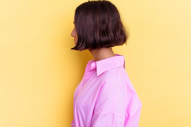 Młoda kobieta rasy mieszanej na białym tle na żółtym tle patrząc w lewo, pozę bokiem.