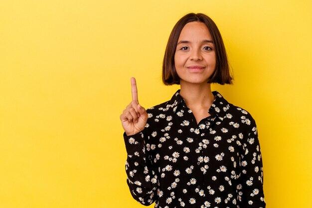 Młoda kobieta rasy mieszanej na białym tle na żółtym tle pokazano numer jeden palcem.