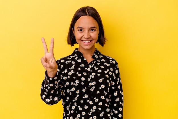 Młoda kobieta rasy mieszanej na białym tle na żółtym tle pokazując znak zwycięstwa i uśmiechając się szeroko.
