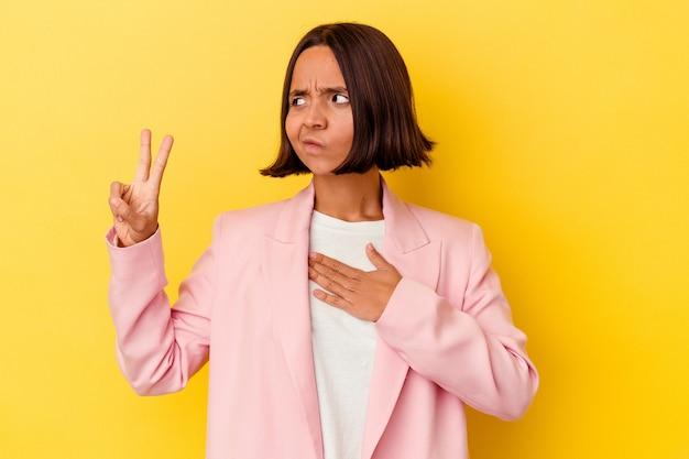 Młoda kobieta rasy mieszanej na białym tle na żółtym tle składa przysięgę, kładąc rękę na klatce piersiowej.