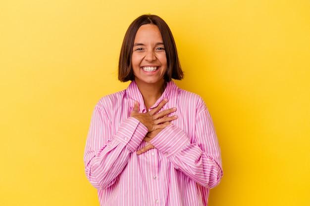 Młoda kobieta rasy mieszanej na białym tle na żółtym tle śmieje się radośnie i dobrze się bawi trzymając ręce na brzuchu.