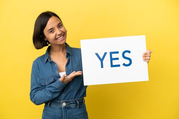 Młoda kobieta rasy mieszanej na białym tle na żółtym tle trzyma tabliczkę z tekstem tak i wskazuje go
