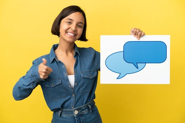 Młoda kobieta rasy mieszanej na białym tle na żółtym tle trzymając plakietkę z ikoną dymka z kciukiem do góry