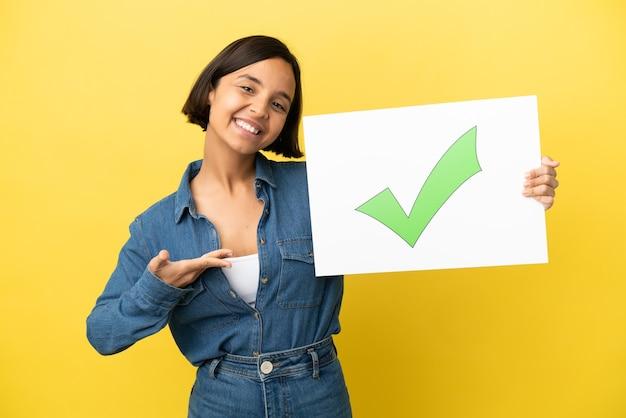 Młoda kobieta rasy mieszanej na białym tle na żółtym tle trzymając plakietkę z tekstem ikona zielonego znacznika wyboru i wskazując ją