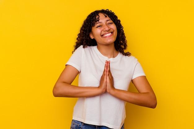 Młoda kobieta rasy mieszanej na białym tle na żółtym tle, trzymając się za ręce w módlcie się blisko ust, czuje się pewnie.