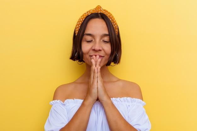 Młoda kobieta rasy mieszanej na białym tle na żółtym tle trzymając się za ręce w modlitwie w pobliżu ust, czuje się pewnie.