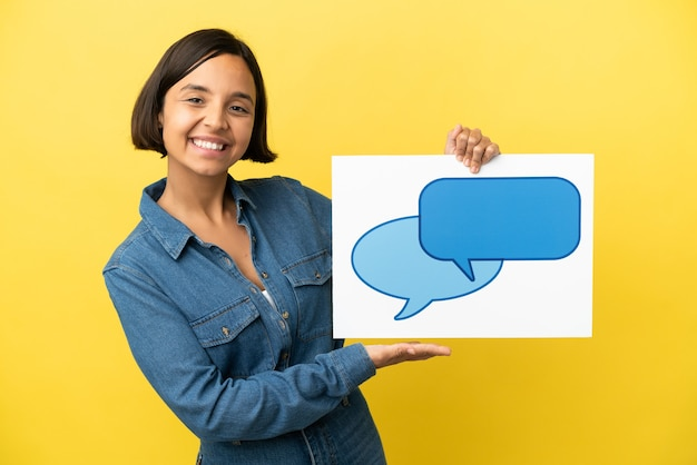 Młoda kobieta rasy mieszanej na białym tle na żółtym tle trzymając tabliczkę z ikoną dymka z happy wypowiedzi