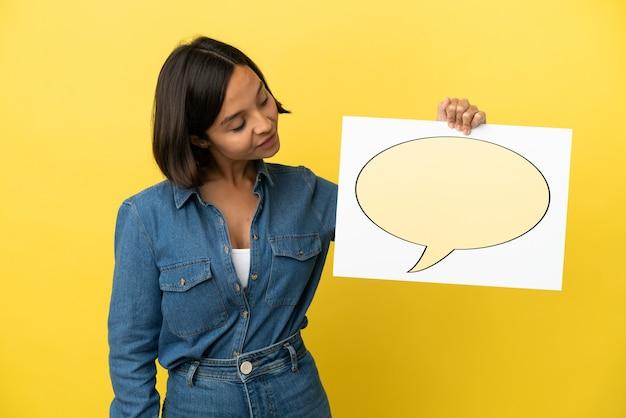 Młoda kobieta rasy mieszanej na białym tle na żółtym tle trzymając tabliczkę z ikoną dymka