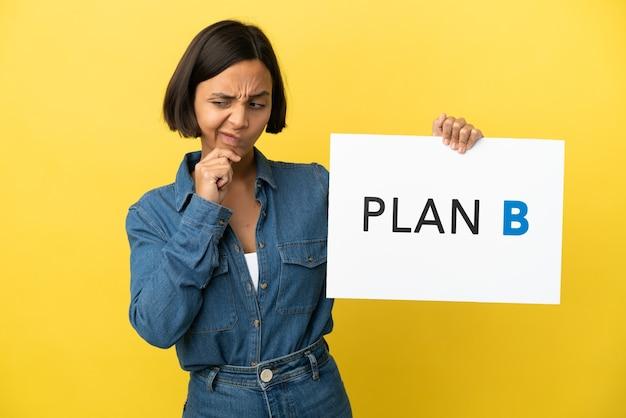 Młoda kobieta rasy mieszanej na białym tle na żółtym tle trzymając tabliczkę z komunikatem plan b i myślenia
