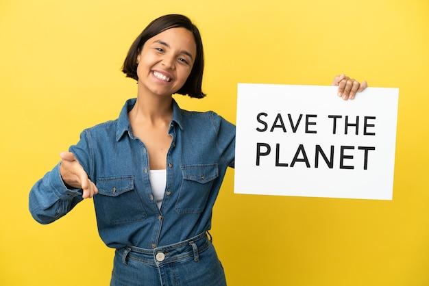 Młoda kobieta rasy mieszanej na białym tle na żółtym tle trzymająca tabliczkę z tekstem save the planet dokonując transakcji