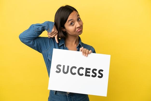 Młoda kobieta rasy mieszanej na białym tle na żółtym tle trzymająca tabliczkę z tekstem sukces i wskazującą go