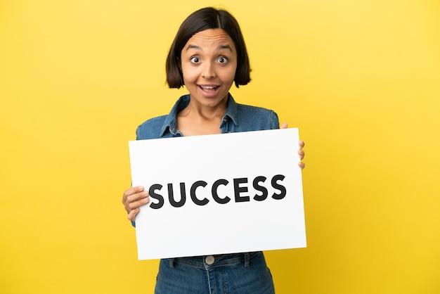 Młoda kobieta rasy mieszanej na białym tle na żółtym tle trzymająca tabliczkę z tekstem sukces ze zdziwioną ekspresją