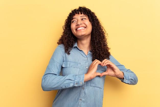 Młoda kobieta rasy mieszanej na białym tle na żółtym tle, uśmiechając się i pokazując kształt serca rękami.