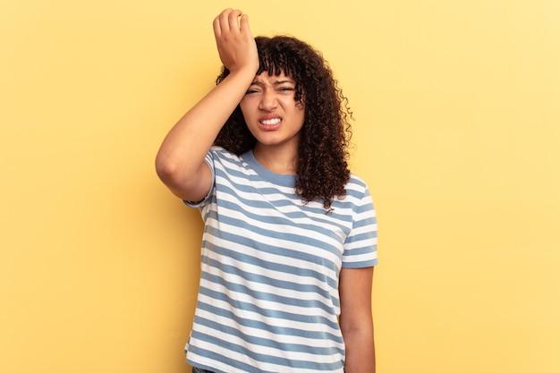 Młoda kobieta rasy mieszanej na białym tle na żółtym tle zapominając o czymś, uderzając dłonią w czoło i zamykając oczy.