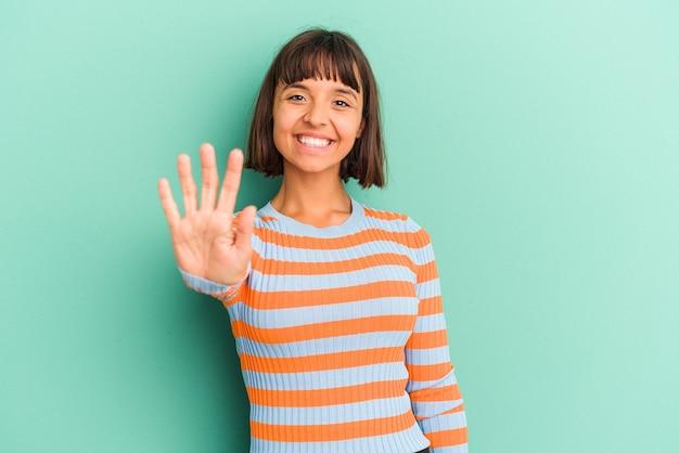 Młoda kobieta rasy mieszanej na białym tle niebieski uśmiechnięty wesoły pokazując numer pięć palcami.