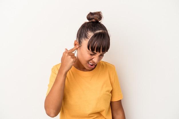 Młoda kobieta rasy mieszanej na białym tle obejmujące uszy rękami.