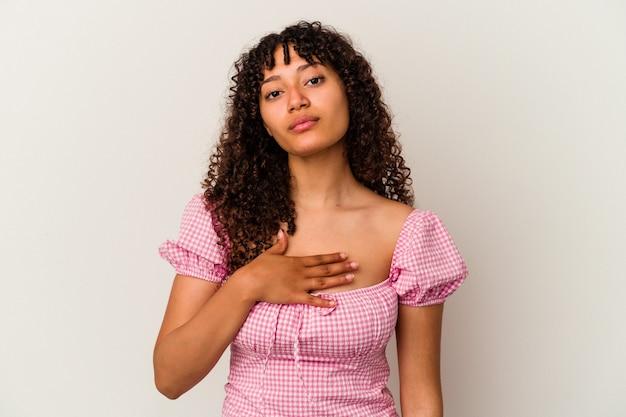 Młoda kobieta rasy mieszanej na białym tle składając przysięgę, kładąc rękę na klatce piersiowej.