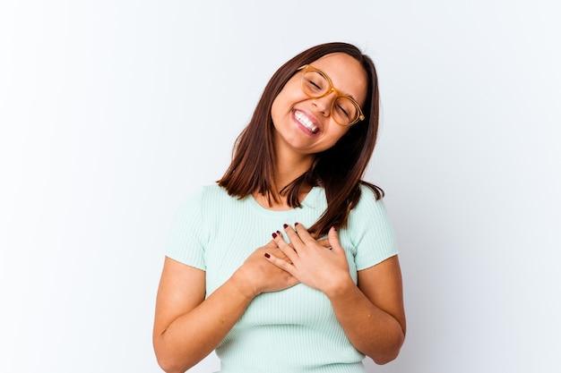 Młoda kobieta rasy mieszanej na białym tle śmiejąc się, trzymając ręce na sercu, pojęcie szczęścia.