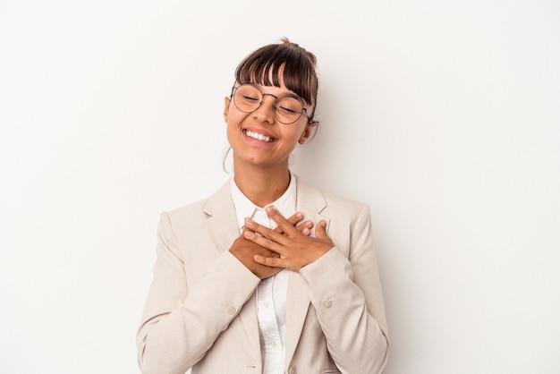 Młoda kobieta rasy mieszanej na białym tle śmiejąc się trzymając ręce na sercu, pojęcie szczęścia.