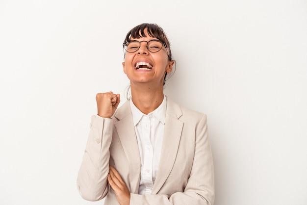 Młoda kobieta rasy mieszanej na białym tle świętuje zwycięstwo, pasję i entuzjazm, szczęśliwy wyraz.