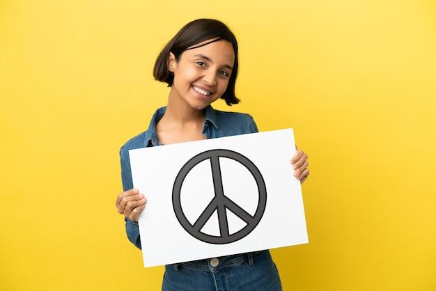 Młoda kobieta rasy mieszanej na białym tle trzymająca afisz z symbolem pokoju ze szczęśliwym wyrazem twarzy