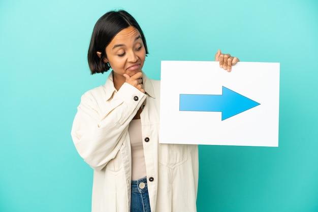 Młoda kobieta rasy mieszanej na białym tle trzymająca tabliczkę z symbolem strzałki i myślącą